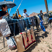 060113       Cable Hoover<br /> <br /> Vendors Creesh Poyer, left, Lambert Poyer and Crystal Atene do business over a fence that marks the edge of private property after other vendors were cited for their proximity to U.S. Highway 566 in Church Rock Saturday.