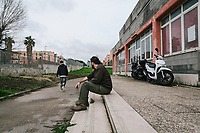 """NAPLES, ITALY - 16 MARCH 2018: Founder and President of """"Il Tappeto di Iqbal"""" Giovanni Savino (38, center) looks at a teenager who missed school and a potential school-dropout as he walks away,  here at """"Il Tappeto di Iqbal"""" (Iqbal's carpet), a non-profit cooperative in Barra, the estern district of Naples, Italy, on March 16th 2018.<br /> <br /> Il Tappeto di Iqbal (Iqbal's Carpet) is a non-profit cooperative founded in 2015 and Save The Children partner since 2015 that operates in the Naple's eastern neighborhood of Barra children in the arts of circus, theater and parkour. It was named after Iqbal Masih, a Pakistani boy who escaped from life as a child slave and became an activist against bonded labor in the 1990s.<br /> Barra, which is home to some 45,000 people, has the highest rate of school dropouts in the Italian region of Campania. Once a thriving industrial community, many of the factories were destroyed in a 1980 earthquake and never rebuilt. The resulting de-industrialization turned Barra into a poor, decaying neighborhood. There are no cinemas, theaters, parks or public spaces in Barra.<br /> The vast majority of children from poor families are faced with the choice of working in the black economy or joining the ranks of the organised crime.<br /> Recently, Save the Children Italy opened a number of educational and social spaces in Barra. The centers, known as Punti Luce, or points of light, aim to help local kids stay out of the ranks of the organised crime and have also become hubs for Iqbal's Carpet to work."""