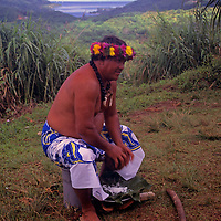 Oceania, South Pacific, French Polynesia, Tahiti. Tahitian islander demonstrates breaking a coconut.