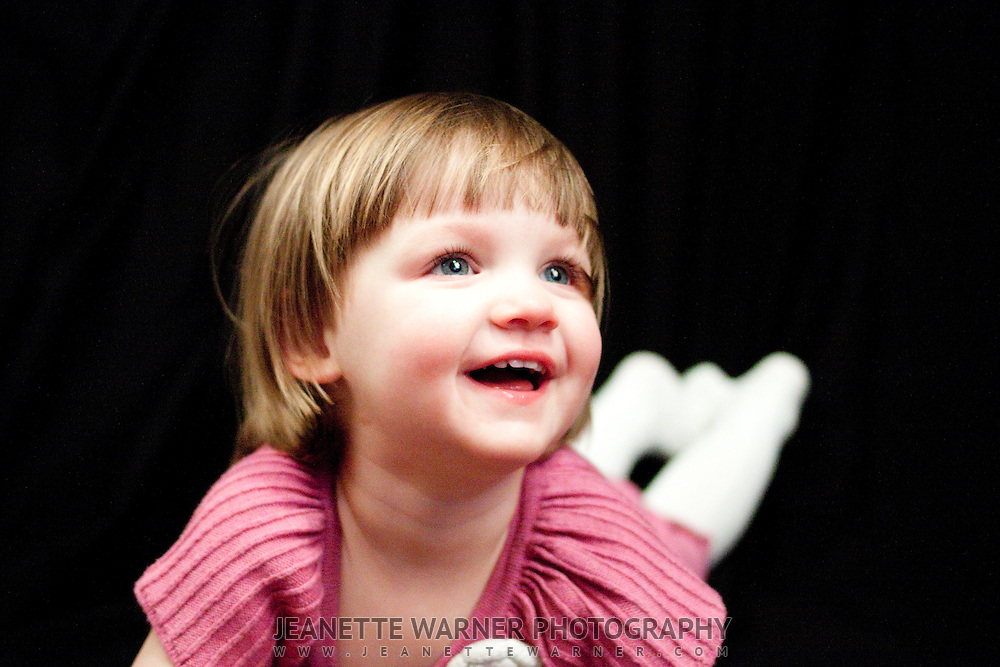 2 year old Ella plays in her bedroom in Lake Fenton, Michigan, for an on-location photo shoot.