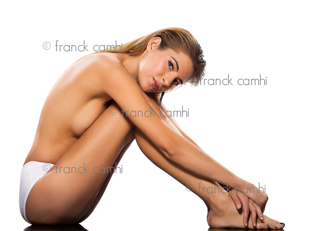 one beautiful topless caucasian woman sitting full length on floor of studio isolated on white background