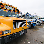 A row of chicken buses behind the Mercado Municipal (town market) in Antigua, Guatemala. From this extensive central bus interchange the routes radiate out across Guatemala. Often brightly painted, the chicken buses are retrofitted American school buses and provide a cheap mode of transport throughout the country.