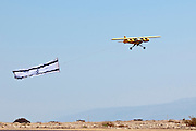 Israel, Massada Air Strip, the international radio controlled model aircraft competition June 27 2009. A model aeroplane trawling the Israeli flag