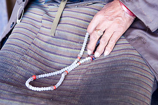 Close of elderly Tibetan Lady's hand with prayer beads outside Temple. Lhasa, Tibet. Asia.