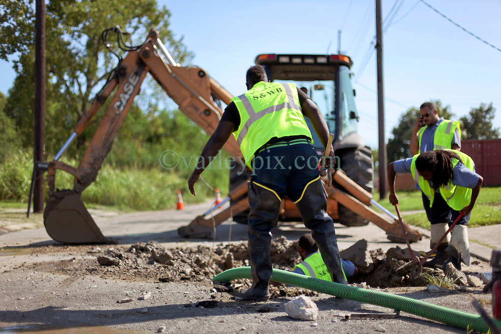 26 August 2015. New Orleans, Louisiana. <br /> Hurricane Katrina revisited. <br /> Rebuilding the Lower 9th Ward a decade later. <br /> Contractors working with the New Orleans Sewerage and Water Board get to work fixing a substantial leak below ground. Signs of a rebirth of the community following the devastation of hurricane Katrina a decade earlier.<br /> Photo credit©; Charlie Varley/varleypix.com.