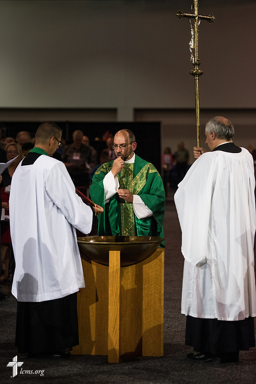 The Rev. Peter C. Bender, pastor of Peace Lutheran Church in Sussex, Wis., reads the Gospel during the Opening Divine Service of the 66th Regular Convention of The Lutheran Church–Missouri Synod on Saturday, July 9, 2016, at the Wisconsin Center in Milwaukee. Bender is joined by the Rev. Will Weedon, chaplain of the LCMS International Center (left) and the Rev. Allen Braun, pastor of Mount Hulda Lutheran Church in Cole Camp, Mo. LCMS/Michael Schuermann