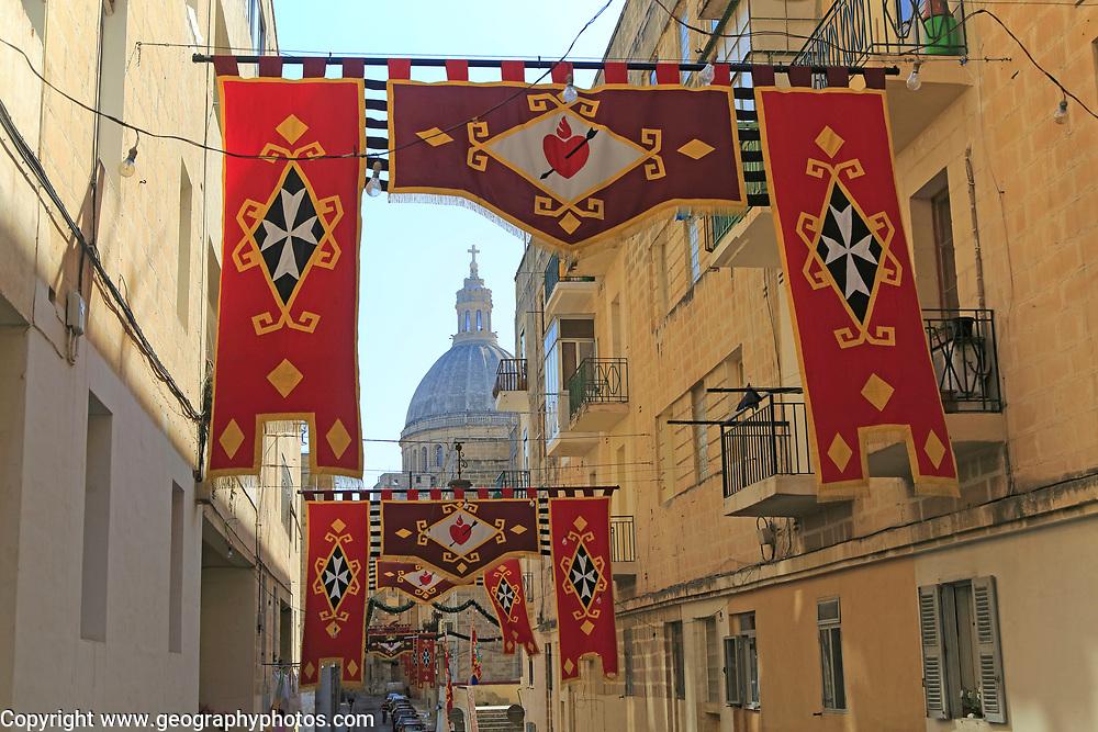 Flags decorate steep historic street in city centre of Valletta, Malta