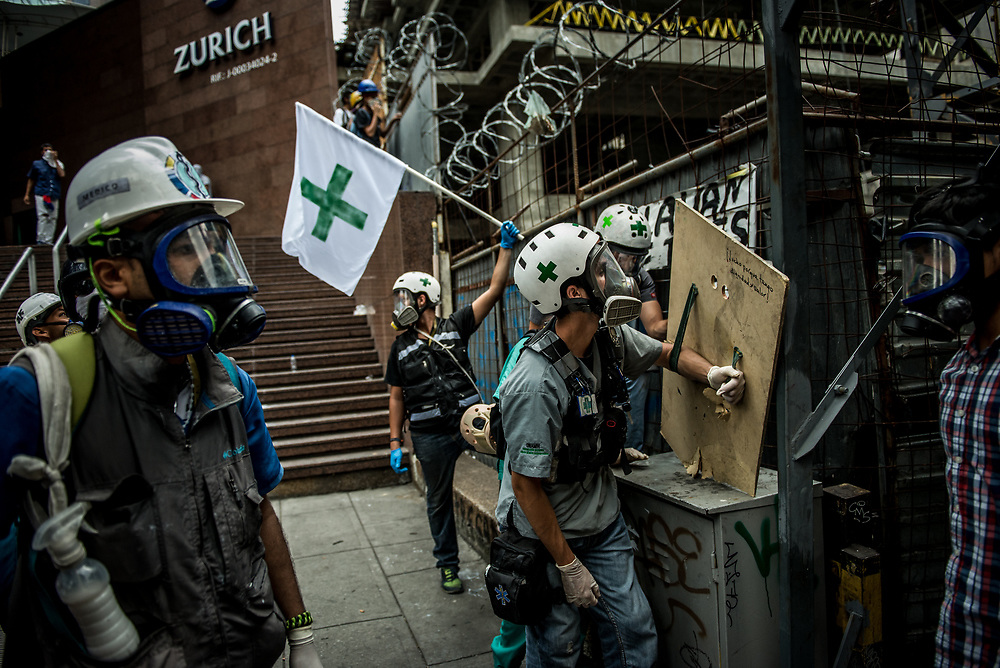 """CARACAS, VENEZUELA - MAY 8, 2017:  Medical students volunteer on the front line of clashes as """"Green Helmets"""" - first responders that evacuate and give first aid to injured protesters.  Many young medical students are angry about the poor state of the public healthcare system.  Over 85 percent of medicines are either impossible, or very difficult to find in Venezuela.  Public hospitals face shortages of even the most basic supplies, like gauze, latex gloves, syringes - even running water. Many say they see volunteering with the Green Helmets as using their talents to supporting the protest movement taking over the streets of Caracas. PHOTO: Meridith Kohut"""