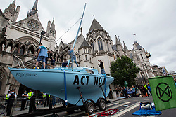 © Licensed to London News Pictures. 15/07/2019. London, UK. Extinction Rebellion protesters raise the mast on top of a boat outside The Royal Courts of Justice. They are campaigning against climate change.  Photo credit: George Cracknell Wright/LNP