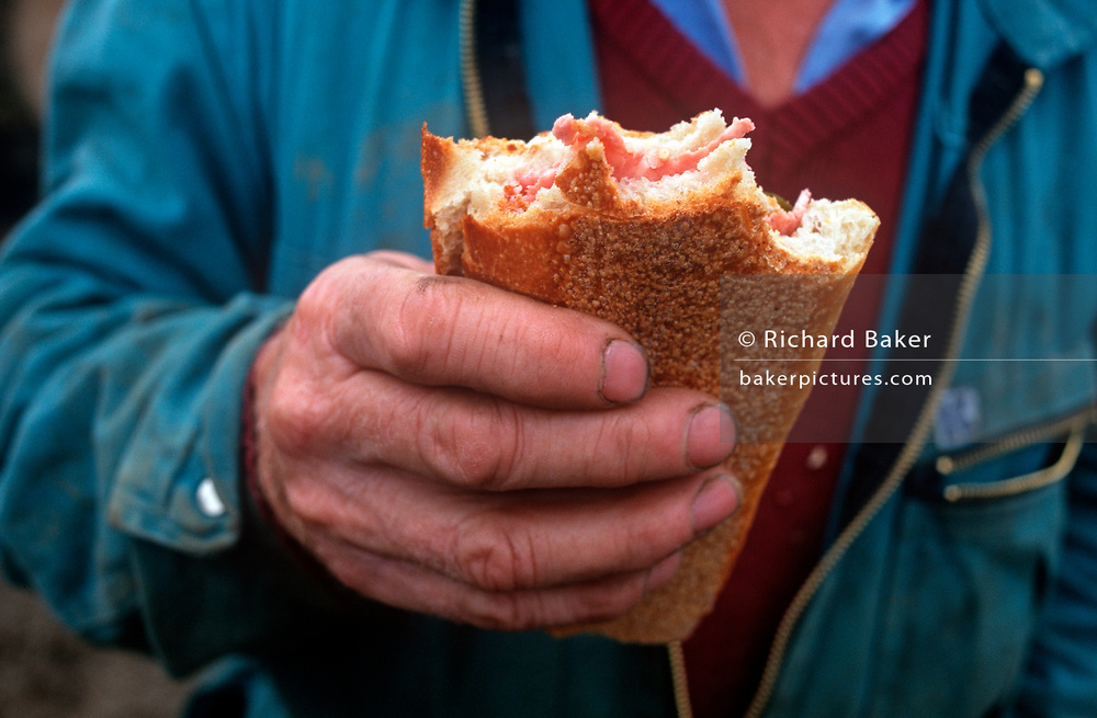 "Detail of a farmer's tough hand holding a crusty ham sandwich during a lunchbreak on the man's land near the Alsace village of Boofzheim, on 13th October 1997, in Boofzheim, France. The farm is in the french village of Boofzheim, a commune in the Bas-Rhin department in Alsace in north-eastern France. Its name is probably derived from the French ""boeuf"" (bull or ox). (Photo by Richard Baker / In Pictures via Getty Images)"