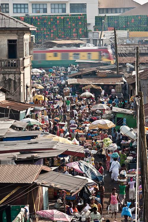 The bustling main thoroughfare of Agbogbloshie, a slum in Ghana's capital, Accra. Head porters, or kaya yei, abound, ferrying loads for paying customers in basins on their heads.