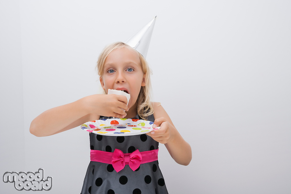 Portrait of cute girl eating birthday cake slice at table in house