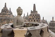 A Buddha statue sits in a lotus position inside an open stupa on the top platform of Borobudur temple. The top level of this monument located in Central Java, Indonesia, has 72 perforated stupas with seated Buddha statues inside.