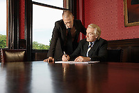 Two Men in Conference Room one leaning over other