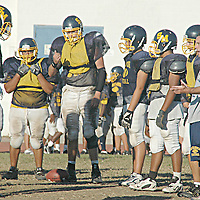 Santa Monica Football Coach Zachary Cuda works through offensive drills with his team during practice on Wednesday
