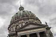 Copenhagen's Marble Church (Marmor Kirke) against a grey, stormy sky.