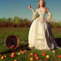 Blonde young woman in period costume standing outdoors with apples spilling out of basket onto grass