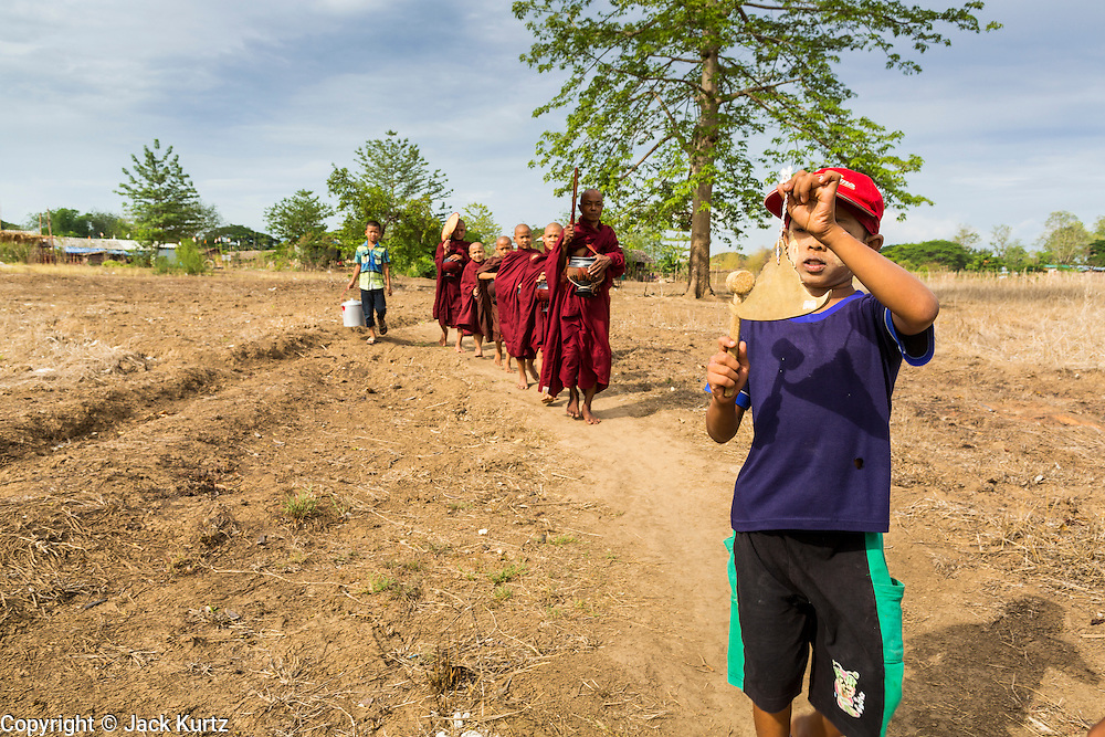 25 MAY 2013 - MAE SOT, TAK, THAILAND:  A Burmese boy rings a prayer gong as he leads a monk and novices through the countryside of an unofficial village of Burmese refugees north of Mae Sot, Thailand. They live on a narrow strip of land about 200 meters deep and 400 meters long that juts into Thailand. The land is technically Burma but it is on the Thai side of the Moei River, which marks most of the border in this part of Thailand. The refugees, a mix of Buddhists and Christians, settled on the land years ago to avoid strife in Myanmar (Burma). For all practical purposes they live in Thailand. They shop in Thai markets and see their produce to Thai buyers. About 200 people live in thatched huts spread throughout the community. They're close enough to Mae Sot that some can work in town and Burmese merchants from Mae Sot come out to their village to do business with them.   PHOTO BY JACK KURTZ