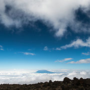 The summit of Mt Meru pokes through the clouds, as seen from about 14,500 feet on Mt Kilimanjaro's Lemosho Route.