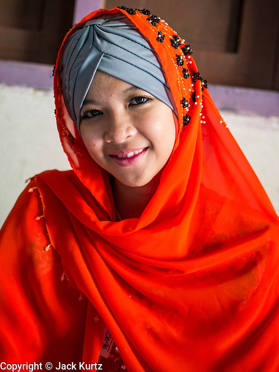 26 OCTOBER 2012 - PULASAIZ, NARATHIWAT, THAILAND:  A Thai Muslim teenager in her best Eid clothing in the villiage Pulasaiz, in the province of Narathiwat, Thailand. Eid al-Adha, also called Feast of the Sacrifice, is an important religious holiday celebrated by Muslims worldwide to honor the willingness of the prophet Ibrahim (Abraham) to sacrifice his firstborn son Ishmael as an act of submission to God, and his son's acceptance of the sacrifice before God intervened to provide Abraham with a ram to sacrifice instead. In 2012 Eid al-Adha was celebrated Oct 25 - 26. People frequently wear the best clothing or buy special outfits for the day.    PHOTO BY JACK KURTZ