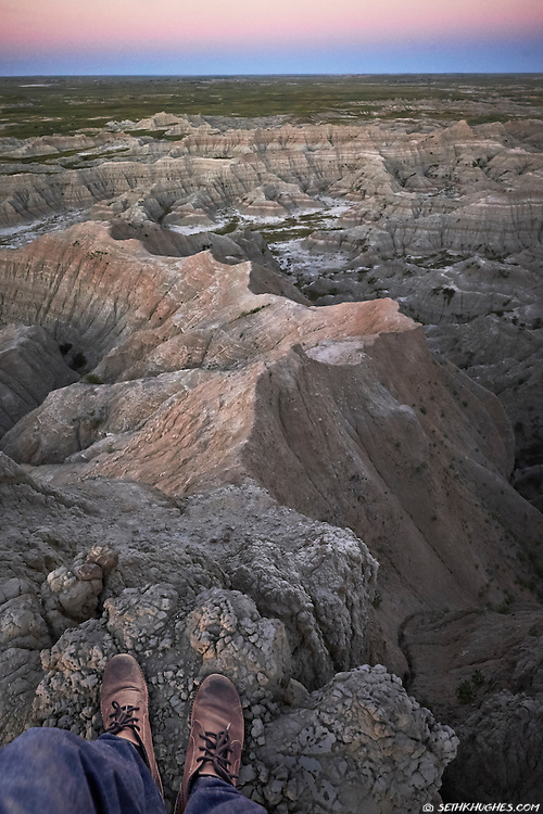 Standing at a viewpoint overlooking Badlands National Park, South Dakota.