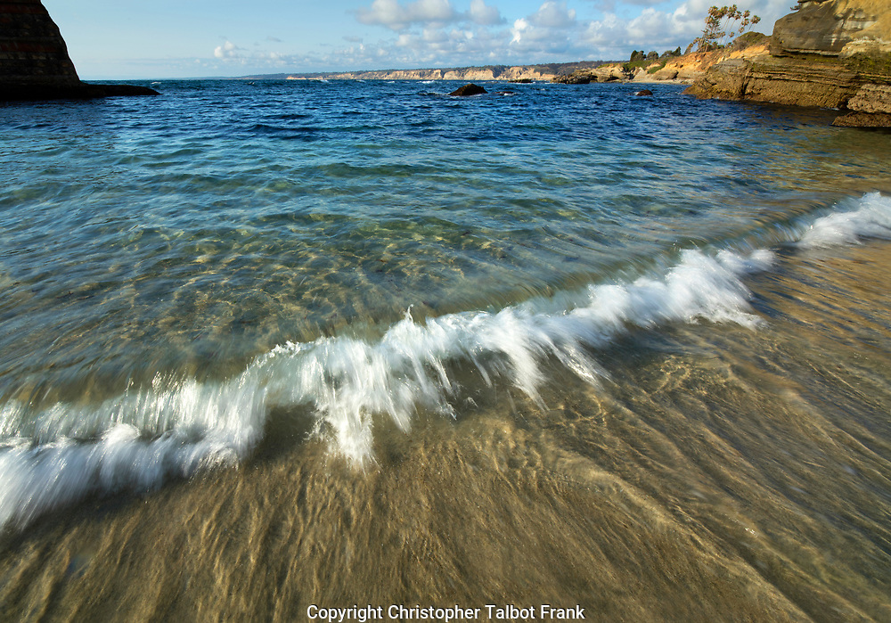 Standing on the beach, I took this photo of a small wave at the protected Children's Pool in La Jolla. The clear blue-green water of the Pacific Ocean is framed by Torrey Pines Cliffs in the background.