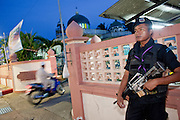 "Sept. 29, 2009 -- YARANG, THAILAND: A Thai Ranger provides security at a Mosque in Yarang as Muslims arrive for evening prayers. The Rangers are a paramilitary unit organized and led by the Thai army.  Thailand's three southern most provinces; Yala, Pattani and Narathiwat are often called ""restive"" and a decades long Muslim insurgency has gained traction recently. Nearly 4,000 people have been killed since 2004. The three southern provinces are under emergency control and there are more than 60,000 Thai military, police and paramilitary militia forces trying to keep the peace battling insurgents who favor car bombs and assassination.   Photo by Jack Kurtz / ZUMA Press"