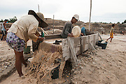 Miners sifting sand searching tin ore.  The entire Batako village works in the illegal mine, mere meters away from the homes.<br /> Illegal tin mine in Batako, Tunghin. Bangka Island (Indonesia) is devastated by illegal tin mines. The demand for tin has increased due to its use in smart phones and tablets.<br /> <br /> <br /> Mine d'étain illégale à Batako - Tunghin. <br /> L'île de Bangka (Indonésie) est dévastée par des mines d'étain sauvages. la demande de l'étain a explosé à cause de son utilisation dans les smartphones et tablettes.