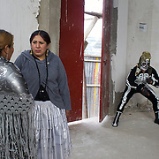 Wrestler Gran Mortis prepares for his bout in the corner of the dressing rooms as Cholita's Martha La Altena (centre) and Claudina the Condemned discuss their upcoming bout against each other  during the 'Titans of the Ring' wrestling group's Sunday performance at El Alto's Multifunctional Centre. Bolivia. The wrestling group includes the fighting Cholitas, a group of Indigenous Female Lucha Libra wrestlers who fight the men as well as each other for just a few dollars appearance money. El Alto, Bolivia, 14th March 2010. Photo Tim Clayton