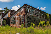 Abandoned Strawn Citrus Packing House District<br /><br />In the late-1800s, the expansion of the railway system into southern Florida opened up the area to new industry and expanded potential business opportunities. Florida was promoted as a paradise on earth, where the &ldquo;climate cured all aliments and the soil produced wealth with little effort&rdquo;. The emerging citrus industry helped in the selling of land as settlers caught &ldquo;orange fever&rdquo;, assuming they could make good money selling to the northern states.<br /><br />At the time, Florida was producing over 5 million boxes of citrus, but it all ended when the state was hit with devastating back-to-back freezes. In 1894 and 1895, temperatures throughout the state dropped, leaving many growers to watch as their crops died out. The first freeze occurred on December 20, 1894. Unfortunately, the state experienced a month of warm weather leaving the citrus groves more vulnerable for the second freeze on February 8, 1895. This event paralyzed the citrus industry and it wouldn&rsquo;t recover from it for a couple more decades.<br /><br />As the citrus industry moved south following the freezes, the few groves which survived gained widespread notoriety. One of these highly reputable groves was Thomas Strawn&rsquo;s &ldquo;Bob White&rdquo; oranges.<br /><br />Back in 1882, Theodore Strawn settled down in West Volusia County and began an orange packing operation. Ever though the freezes of 1894-1895 eradicated most of the livelihoods of the farmers nearby, the business continued to prosper. In 1921, the original wooden packing house burned down and it was replaced by a new state-of-the-art steel building with a distinctive saw tooth roof line.<br /><br />The next few decades were kind to the Strawn family as the business grew. Of the oranges they grew, only the best were given the &ldquo;Bob White&rdquo; mark, named after the Northern Bobwhite quails the Strawn family enjoyed hunting. While the &ldquo;Bo
