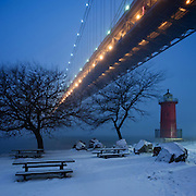 December 26, 2010 - New York, NY : Icy wind and snow whip down the Hudson River, beneath the George Washington Bridge and past the little red lighthouse on Manhattan at dusk on the day after Christmas...The Boxing Day storm pummeled the Eastern seaboard, burying New York City under over a foot of snow.<br /> <br /> This image is a JOURNALISTIC vertically stitched composite image. It is composed of three photographs taken in short succession with a shift (PC) lens and combined using PTGUI software.