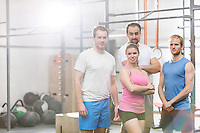 Portrait of confident men and women standing at crossfit gym