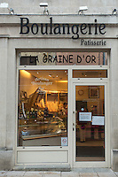Street view of a boulangerie or bakery in   France. Inside one window freshly baked loaves of bread are displayed in warm light.