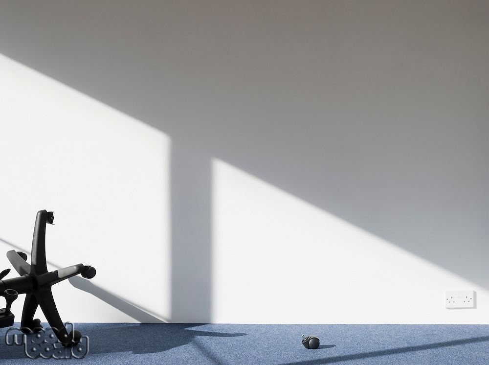 Broken office chair casting shadow on wall