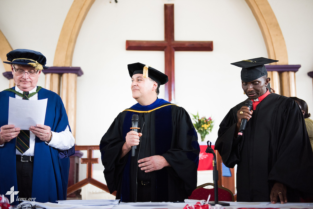 The Rev. Dr. Lawrence R. Rast, Jr., president of Concordia Theological Seminary, Fort Wayne, Ind., speaks during the graduation of 21 pastors and seven deaconesses on Saturday, March 14, 2015, at the Evangelical Lutheran Church in Tanzania – South-East of Lake Victoria Diocese's (ELCT-SELVD) Ebenezer Cathedral in Shinyanga, Tanzania. To the left is the Rev. Dr. Timothy Quill, professor and director of International Studies at CTS, and to the right is Bishop Emmanuel Makala. LCMS Communications/Erik M. Lunsford