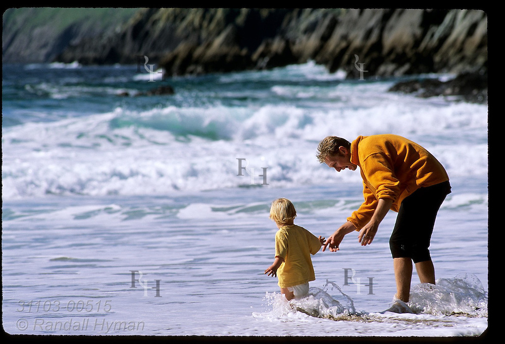Dad & diaper girl wade in the chilly North Atlantic surf of Coumeenole Beach; Dunmore Head, Dingle Peninsula, Ireland.