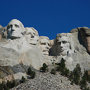 The Mount Rushmore National Memorial, near Keystone, South Dakota, is a monumental granite sculpture by Gutzon Borglum. The monument represents the first 150 years of the history of the United States of America with 60-foot (18 m) sculptures of the heads of former United States presidents (left to right): George Washington, Thomas Jefferson , Theodore Roosevelt, and Abraham Lincoln. The entire memorial covers 1,278.45 acres (5.17 km2) and is 5,725 feet (1,745 m) above sea level.