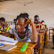 LÉGENDE: BTS génie civil 1ère année mécanique. Pendant la correction du devoir surveillé de mécanique et remises des copies aux étudiants. LIEU: CERFER, Lomé, Togo. PERSONNE(S): Une étudiante en train de faire son devoir.