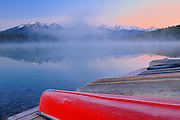 Canoes and Pyramid Lake in fog at dawn<br /> Jasper National Park<br /> Alberta<br /> Canada