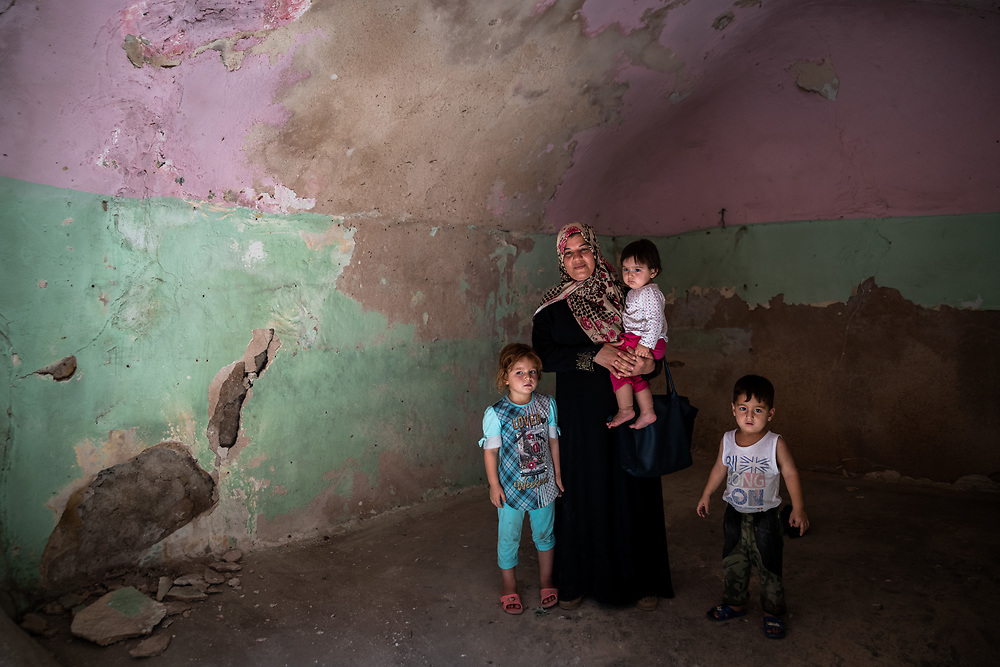 9 August 2018 – Mosul – Iraq – Mother of three Entesar, 32, stands with her children inside their damaged home in the Myasa neighbourhood of Mosul's Old City. Entesar's home is one of the houses that will be rehabilitated with the support of UNDP's Funding Facility for Stabilization (FFS). <br /> <br /> © UNDP Iraq / Claire Thomas