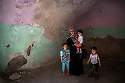 9 August 2018 &ndash; Mosul &ndash; Iraq &ndash; Mother of three Entesar, 32, stands with her children inside their damaged home in the Myasa neighbourhood of Mosul&rsquo;s Old City. Entesar&rsquo;s home is one of the houses that will be rehabilitated with the support of UNDP&rsquo;s Funding Facility for Stabilization (FFS). <br /> <br /> &copy; UNDP Iraq / Claire Thomas