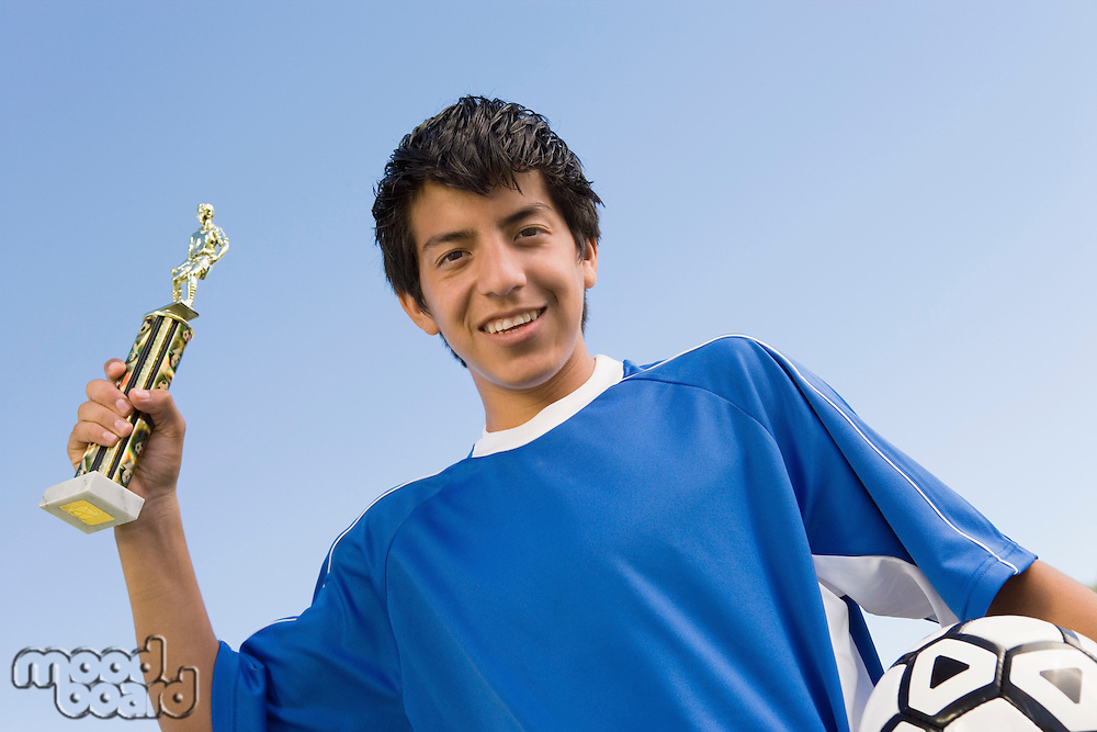 Soccer Player Holding Trophy and Ball