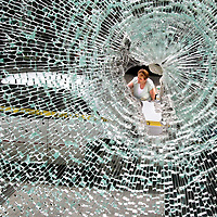 Roxie Jones is visible through a shattered window in the Rittenhouse Building in downtowntown Santa Cruz on May 2, as she tries to remove paint splattered on her car by rioters. A May Day rally turned ugly when protesters rioted, causing more than $100,000 of damage to businesses along Pacific Avenue the previous night.
