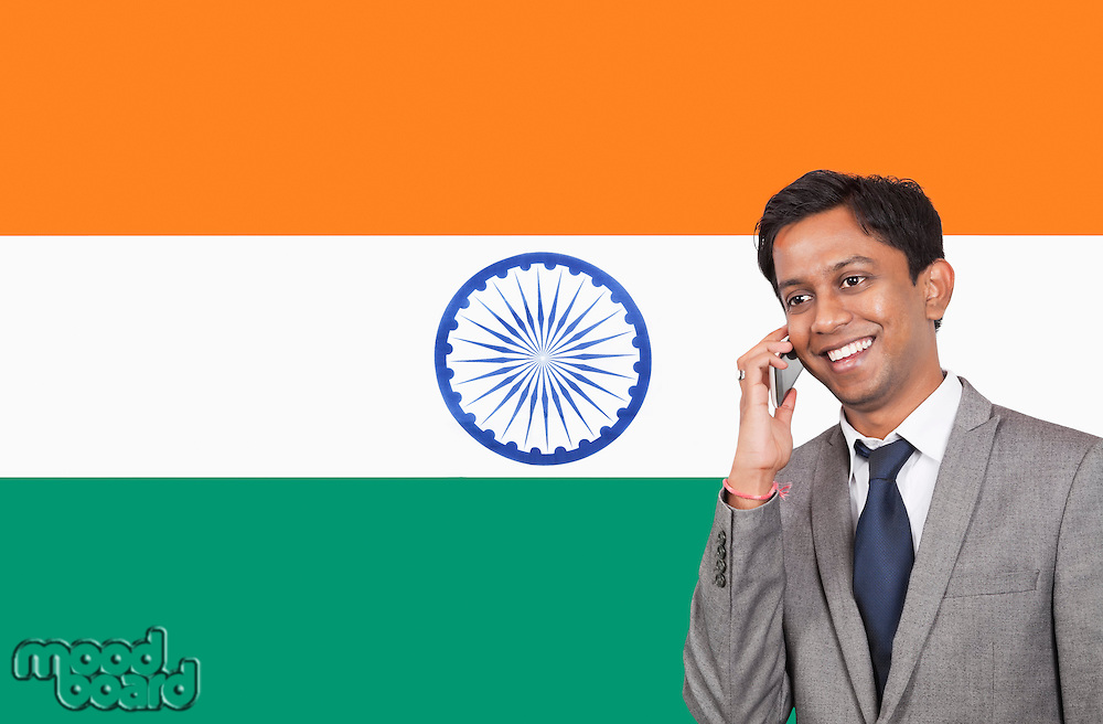 Young businessman using cell phone over Indian flag