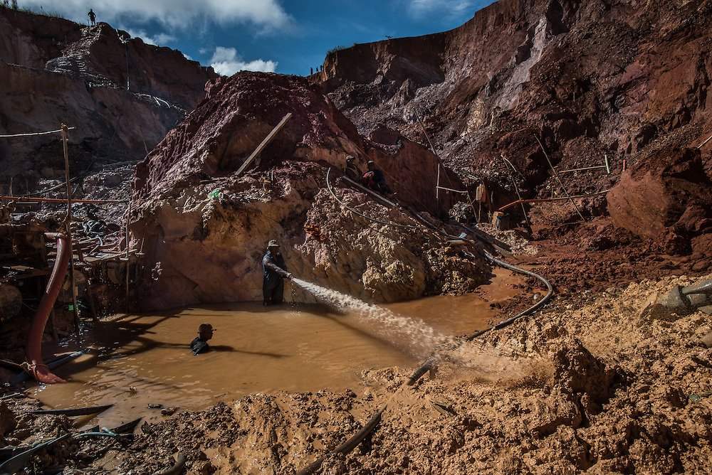 """LAS CLARITAS, VENEZUELA - JULY 20, 2016:  Carlos Raphael, 50, (center, with hose) and his crew illegally mine for gold at the """"Cuatro Muertos"""" (""""Four Dead"""") mine, named so because four miners have died here since the mine was dug.  Raphael has contracted malaria ten times, and said everyone in his crew has also had it multiple times.  Thousands of Venezuelans are flocking to illegal gold mines, like this one, in hopes of surviving the current economic crisis by earning in gold instead of the national currency, whose value steadily falls due to the world's highest inflation.  From this remote part of the jungle the migrant miners have become the vectors of a new epidemic of malaria, because the hot, swampy conditions of the mines make for an ideal breeding ground for mosquitos. Miners spread the disease as they return home with earnings or pay visits to family members. The economic crisis has also left the government without the financial resources to control the disease - they are unable to fumigate homes, provide medicines to everyone that is sick, or even to test all patients with symptoms of malaria in many places. PHOTO: Meridith Kohut for The New York Times"""