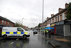 A police van is parked across the area of Claremont Road, Moss Side, Manchester, where several people have been injured after a shooting.