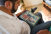 A painful memory - Palestinian peace activist Rani Burnat looks at a photo of himself on the day he was shot in the neck by an Israeli soldier. The injury has left him paralysed from the chest.