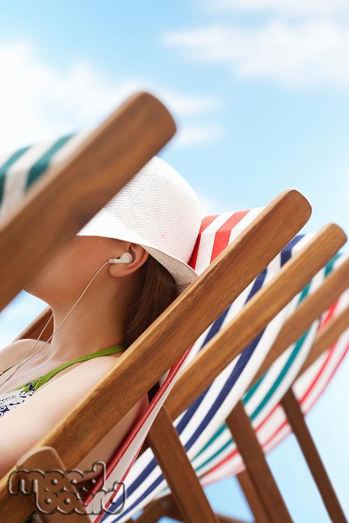 Woman wearing earphones sitting in deckchair side view