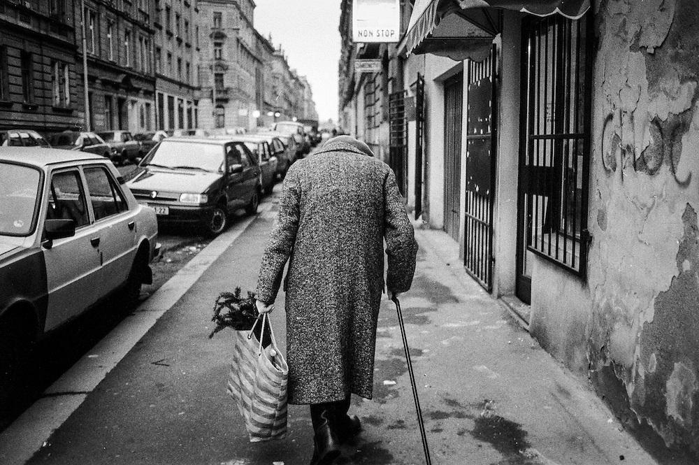 An old lady preparing for the Christmas celebration walking Borivojova street.