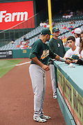 ANAHEIM, CA - JULY 21:  Coco Crisp #4 of the Oakland Athletics signs an autograph before the game against the Los Angeles Angels of Anaheim on Sunday, July 21, 2013 at Angel Stadium in Anaheim, California. The Athletics won the game in a 6-0 shutout. (Photo by Paul Spinelli/MLB Photos via Getty Images) *** Local Caption *** Coco Crisp